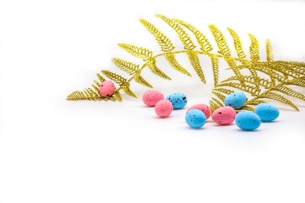 Wielkanocni kolorowi jajka i złocista paproć rozgałęziają się na białym tle Premium Zdjęcia