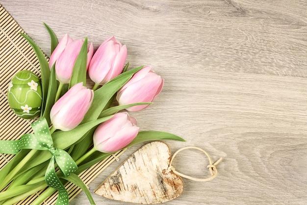 Wielkanocny projekt z tulipanami, jajkiem i drewnianym sercem Premium Zdjęcia