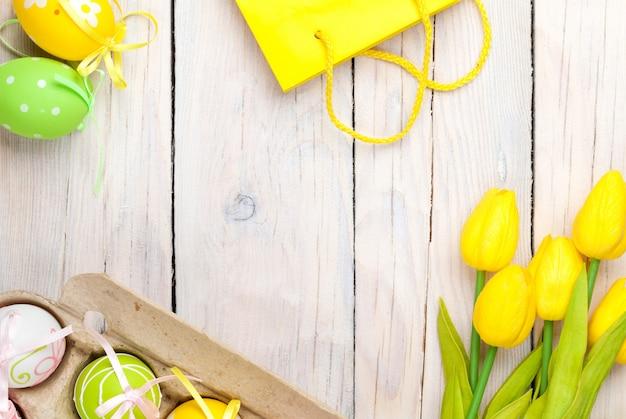 Wielkanocny Tło Z Kolorowymi Jajkami I żółtymi Tulipanami Premium Zdjęcia