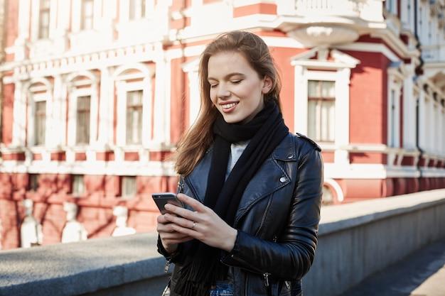 Wielkomiejskie życie. Portret Uroczej Stylowej Kobiety Stojącej Na Ulicy, Trzymając Smartfon I Sms-y Darmowe Zdjęcia