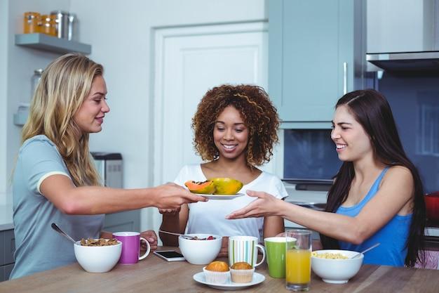 Wielo- etniczni przyjaciele trzyma talerza z melonowem w domu Premium Zdjęcia