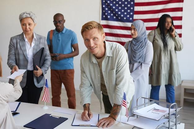 Wieloetniczna Grupa Osób Rejestrujących Się W Lokalu Wyborczym Ozdobionym Amerykańskimi Flagami W Dniu Wyborów, Skup Się Na Uśmiechniętym Mężczyźnie Podpisującym Karty Do Głosowania I Skopiuj Miejsce Premium Zdjęcia
