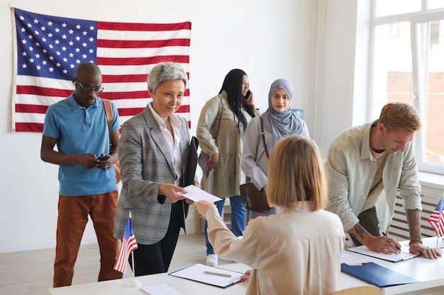 Wieloetniczna Grupa Osób Rejestrujących Się W Lokalu Wyborczym Udekorowana Amerykańskimi Flagami W Dniu Wyborów, Miejsce Na Kopię Premium Zdjęcia
