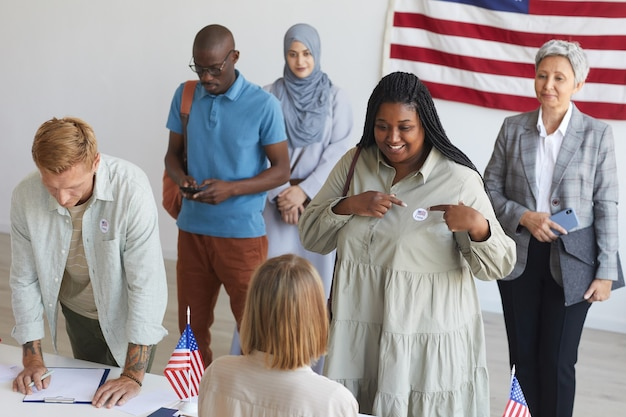 Wieloetniczna Grupa Osób Rejestrujących Się W Lokalu Wyborczym Udekorowana Amerykańskimi Flagami W Dniu Wyborów, Skupienie Się Na Uśmiechniętej Afrykańskiej Kobiecie Wskazującej Na Naklejkę I Głosuję, Miejsce Na Kopię Premium Zdjęcia