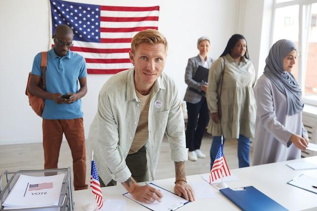 Wieloetniczna Grupa Osób Rejestrujących Się W Lokalu Wyborczym Udekorowanym Amerykańskimi Flagami W Dniu Wyborów, Skupienie Się Na Podpisywaniu Kart Do Głosowania Przez Młodego Mężczyznę I Skopiowanie Miejsca Premium Zdjęcia