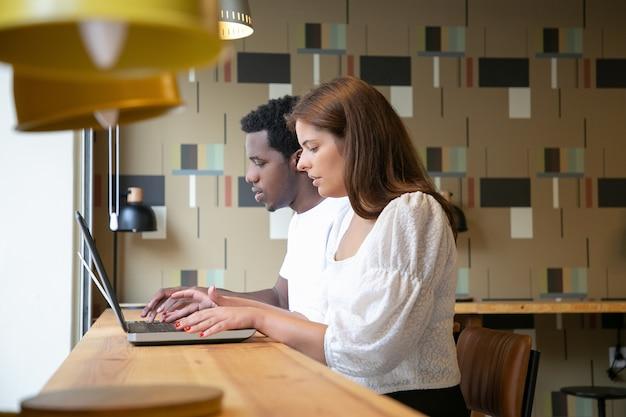 Wieloetniczni Projektanci Siedzący Razem I Pracujący Na Laptopach W Przestrzeni Coworkingowej Darmowe Zdjęcia