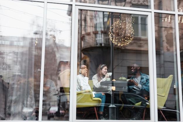 Wielokulturowi Przyjaciele Siedzący Obok Okna Darmowe Zdjęcia