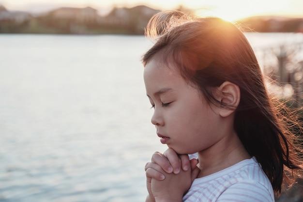 Wielokulturowy małej dziewczynki modlenie z sunflare tłem Premium Zdjęcia