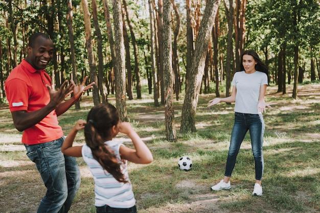Wielonarodowa Rodzina Gra Z Piłką W Lesie. Premium Zdjęcia