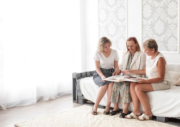 Wielopokoleniowe kobiety patrzeje album fotograficzny wpólnie podczas gdy siedzący na kanapie Darmowe Zdjęcia