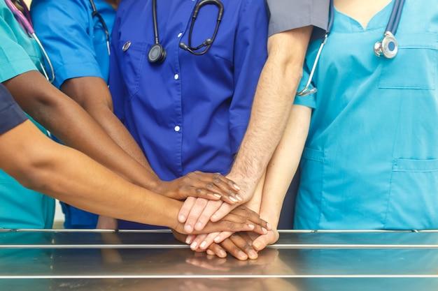 Wielorasowy Zespół Młodych Lekarzy Układających Ręce W Pomieszczeniach. Grupa Zespołu Chirurgii Wielorasowego Doktor Układanie Rąk W Sali Operacyjnej Premium Zdjęcia