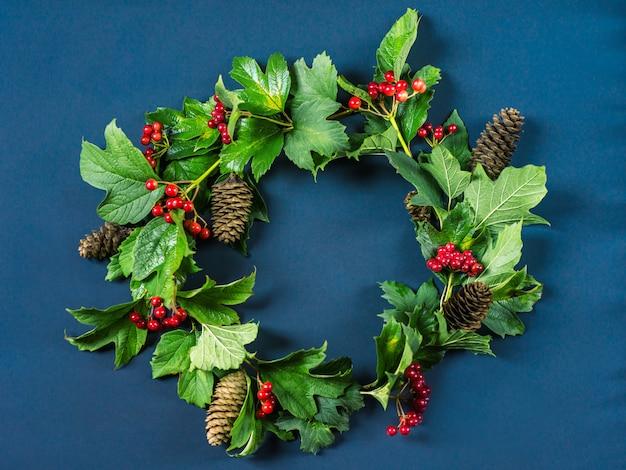Wieniec Bożonarodzeniowy, Gałąź Z Czerwonymi Jagodami, Zielone Liście I Szyszki Jodły Premium Zdjęcia