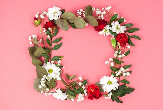 Wieniec wykonane z czerwonych i białych kwiatów przed brzoskwiniowym tle Darmowe Zdjęcia