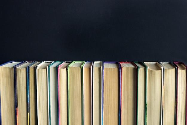 Wiersz stos starych książek na tle czarnej tablicy Premium Zdjęcia