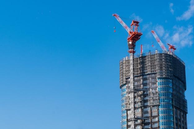 Wierzchołek budowa z żurawiami na niebieskiego nieba tle z kopii przestrzenią Premium Zdjęcia