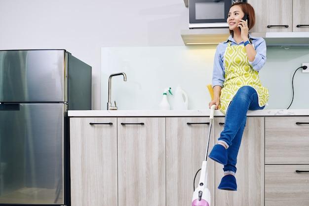 Wietnamska Gospodyni Domowa Z Odkurzaczem W Ręku Siedzi Na Kuchennym Blacie I Rozmawia Przez Telefon Z Przyjacielem Premium Zdjęcia