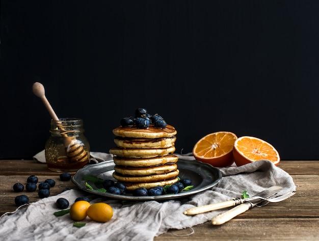Wieża Naleśnikowa Ze świeżymi Jagodami, Pomarańczami I Miętą Na Rustykalnym Metalowym Talerzu. Premium Zdjęcia