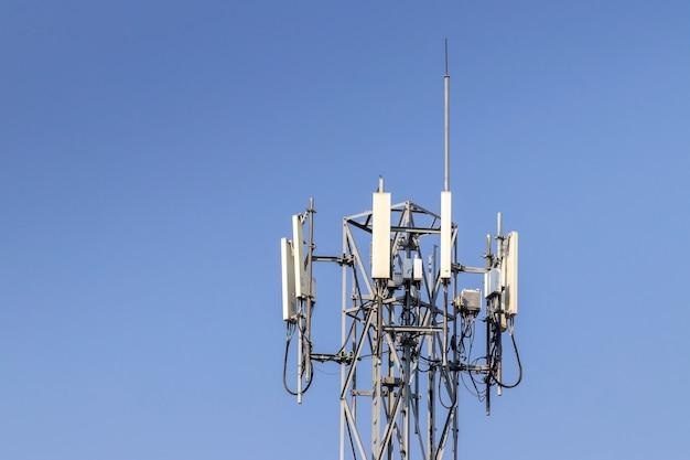 Wieża Telekomunikacyjna Z Niebieskim Tle Nieba I Białych Chmur, Technologia Komunikacji Słupa Satelitarnego. Premium Zdjęcia