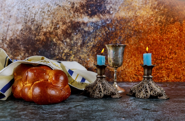 Wigilia szabatowa z chlebem chałła, świecami szabatowymi i kieliszkiem do wina kidusz. Premium Zdjęcia