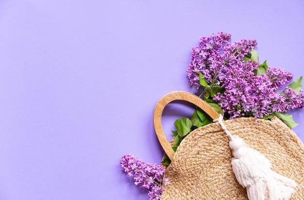 Wiklinowa torebka z kwiatami bzu, wiosna, koncepcja kreatywna lato, fioletowe tło, kopia przestrzeń, widok z góry Premium Zdjęcia
