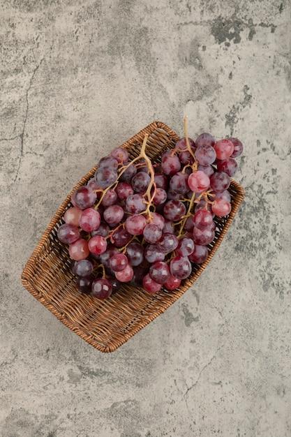 Wiklinowy Kosz Pysznych Czerwonych Winogron Na Marmurowym Stole. Darmowe Zdjęcia