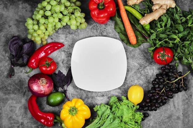 Winogrona, Papryka, Zielenie, Cytryna, Pomidor, Imbir I Biały Talerz Na Marmurowym Tle. Darmowe Zdjęcia