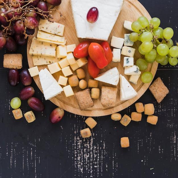 Winogrona, Pomidory, Bloki Sera I Pomidory Czereśniowe Na Desce Nad Teksturą Darmowe Zdjęcia