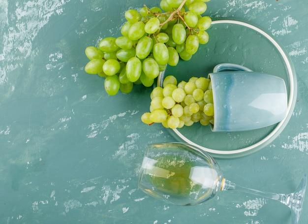Winogrona W Filiżance Z Napojem Płasko Leżały Na Tle Tynku I Tacy Darmowe Zdjęcia