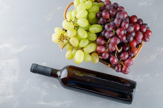 Winogrona Z Butelką Napoju W Koszu Na Tynku, Leżał Na Płasko. Darmowe Zdjęcia