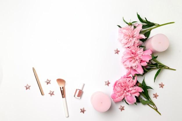 Wiosenna kompozycja kwiatów piwonii, różowych świec, akcesoriów damskich Premium Zdjęcia
