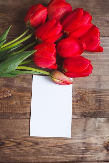 Wiosenne Kwiaty. Bukiet Czerwonych Tulipanów Z Kartą Na Brązowy Drewniany Stół. Koncepcja Dzień Matki I Walentynki. Leżał Płasko Premium Zdjęcia