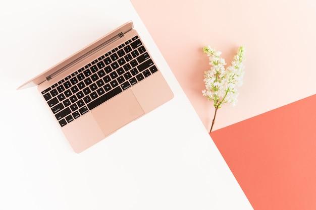 Wiosenne kwiaty bzu i różowy laptop na kobiecym pastelowym biurku. Premium Zdjęcia