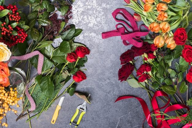Wiosenne Kwiaty Na Kamiennym Stole. Koncepcja Tworzenia Bukietów Róż, Tulipanów. Kwiaciarnia W Miejscu Pracy Premium Zdjęcia