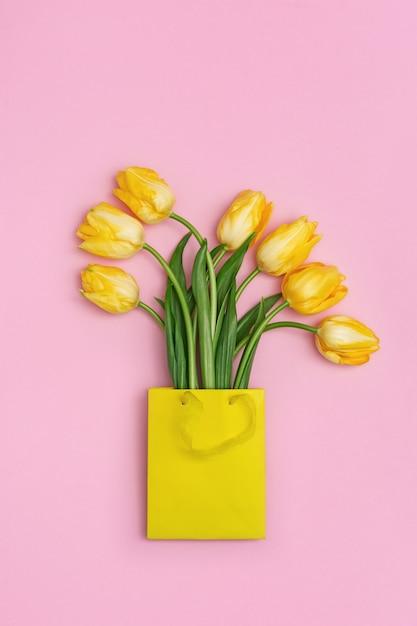 Wiosenny Kwiat żółty Tulipan W Papierowej Torebce Prezent Na Różowej Powierzchni. Naturalny świeży Bukiet Kwiatów Z Kopii Przestrzenią. Jasne Kolory I Minimalny Styl. Widok Z Góry. Leżał Płasko Premium Zdjęcia