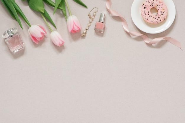 Wiosna Koncepcja Transparent Na Blogu. Różowe Tulipany, Lakier Do Paznokci, Woda Toaletowa I Bransoletka Na Zakurzonym Beżowym Tle Z Miejsca Kopiowania. Blogowanie Modowe Premium Zdjęcia
