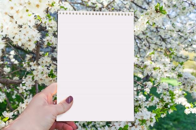 Wiosny lato mockup z białym notatnikiem w żeńskiej ręce Premium Zdjęcia