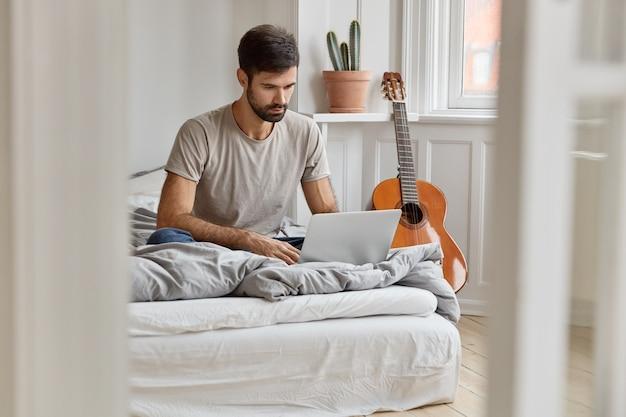 Wizerunek Atrakcyjnego Młodzieńca Siedzi W Wygodnym łóżku, Synchronizuje Pliki Multimedialne Na Laptopie, Pracuje Jako Wolny Strzelec W Domu, Spędza Wolny Czas Oglądając Filmy, Odpoczywa W Przytulnym Mieszkaniu. Darmowe Zdjęcia