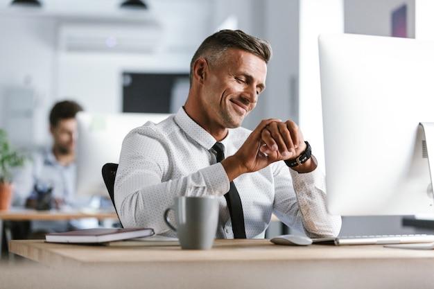 Wizerunek Dorosłego Biznesmena Lat 30. Na Sobie Białą Koszulę I Krawat Siedzi Przy Biurku W Biurze Przy Komputerze I Patrząc Na Zegarek Premium Zdjęcia