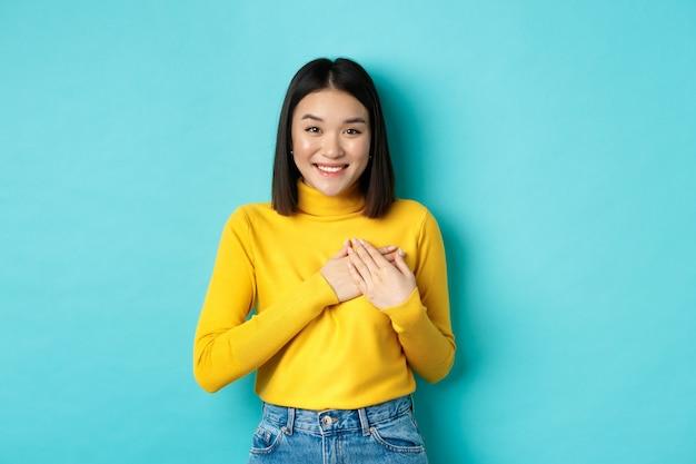 Wizerunek Pięknej Azjatyckiej Kobiety Trzymającej Się Za Ręce Na Sercu I Uśmiechniętej, Dziękując, Czując Wdzięczność, Stojąc Na Niebieskim Tle Premium Zdjęcia