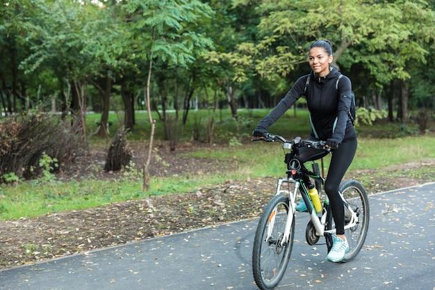 Wizerunek Pięknej Kobiety Spaceru Na Rowerze W Parku Na świeżym Powietrzu. Premium Zdjęcia