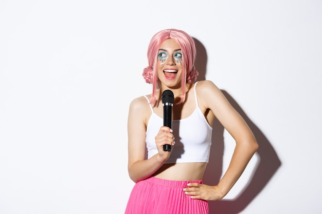 Wizerunek Pięknej Uśmiechniętej Dziewczyny W Różowej Peruce, śpiewającej Piosenkę W Mikrofonie, Na Sobie Kostium Na Halloween Na Imprezę, Na Stojąco. Darmowe Zdjęcia