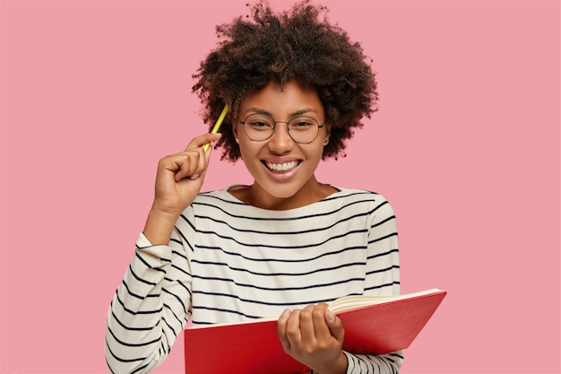 Wizerunek Pięknej Wesołej Dziewczyny Z Uśmiechem Toothy Zapisuje Notatki W Notatniku Ołówkiem Darmowe Zdjęcia