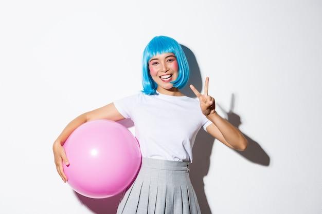 Wizerunek ślicznej Azjatki W Niebieskiej Peruce I Kostiumie Na Halloween, Pokazujący Gest Pokoju, Trzymający Duży Różowy Balon. Darmowe Zdjęcia