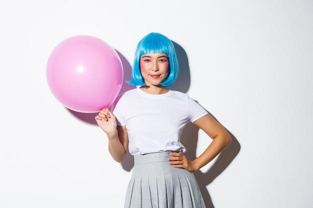 Wizerunek Zalotnej, Bezczelnej Azjatki W Niebieskiej Peruce, Ubranej Na Imprezę, Trzymającej Duży Różowy Balon I Pewnie Uśmiechającej Się Do Kamery. Darmowe Zdjęcia