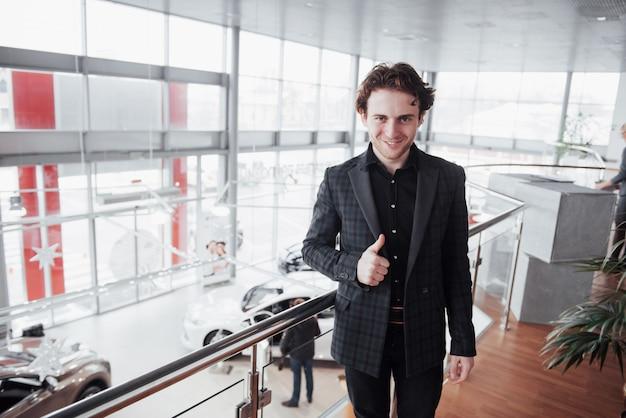 Wizyta w salonie samochodowym. młody człowiek w salonie samochodowym. szczęśliwy człowiek pokazuje palcem w górę Premium Zdjęcia