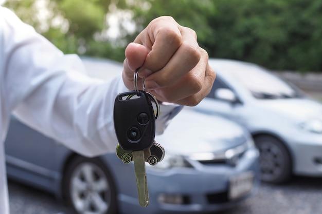 Właściciel samochodu przekazuje kupujący kluczyki do samochodu. sprzedaż samochodów używanych Premium Zdjęcia