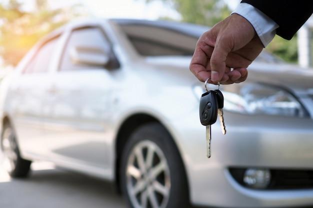 Właściciel samochodu ustawia kluczyki do kupującego. sprzedaż samochodów używanych Premium Zdjęcia