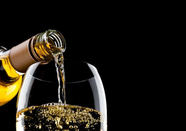 Wlewanie Białego Wina Z Butelki Do Szklanki Na Białym Tle Premium Zdjęcia