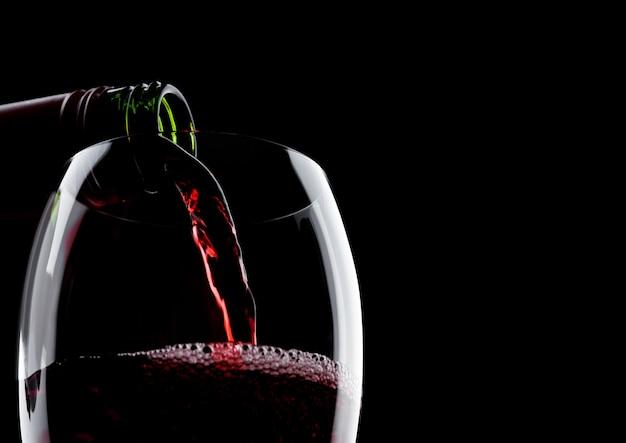 Wlewanie Czerwonego Wina Z Butelki Do Szklanki Izolowane Premium Zdjęcia