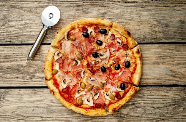 Włoska Pizza Z Boczkiem, Pieczarkami, Oliwkami, Pomidorami Na Tle Drewna Premium Zdjęcia